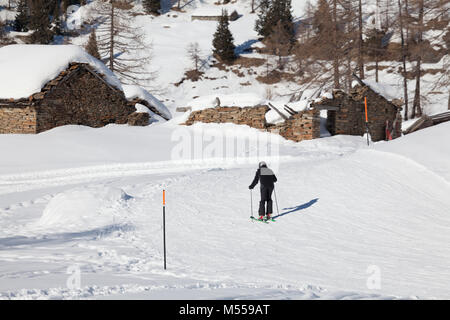 Isolated Skier skiing near a abandoned and snowy old cottage in mountain during the winter season. - Stock Photo