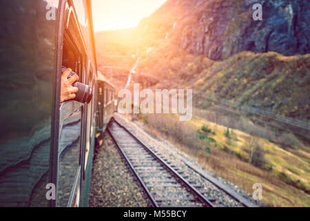 Taking pictures of landscape from a train window - Stock Photo