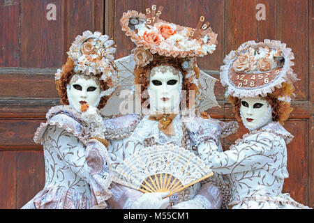 Three costumed people dressed like time during the Carnival of Venice (Carnevale di Venezia) in Venice, Italy - Stock Photo