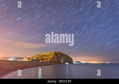 Star trails over West Bay in Dorset - Stock Photo