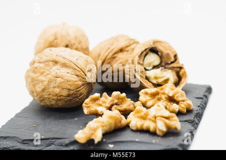 Several walnuts both in their shells and (un) shelled on black slate stone plate, whole setup isolated on white - Stock Photo