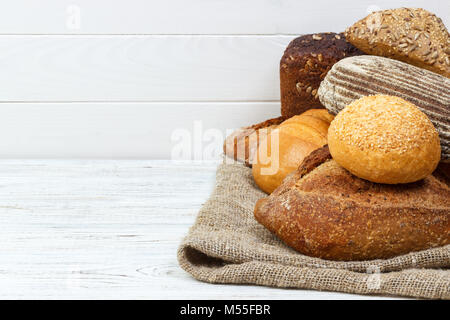 Plenty bread background. Bakery and grocery concept. Fresh, healthy rye and white loaves, sprinkled flour on sackcloth - Stock Photo