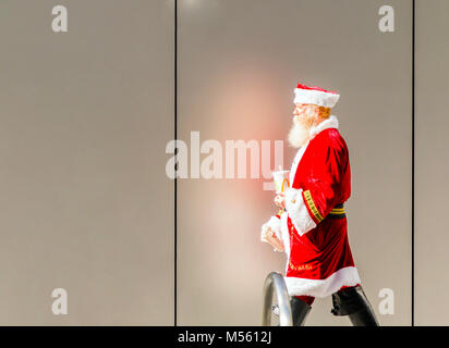 San Francisco, CA, USA, october 2016: elderly man disguised as Santa Claus taking a break walking in the streets - Stock Photo