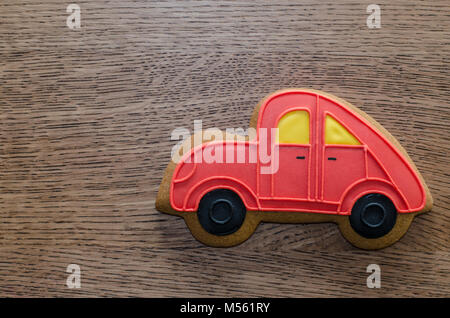 Close-up of red gingerbread car lying on the wooden table background - Stock Photo
