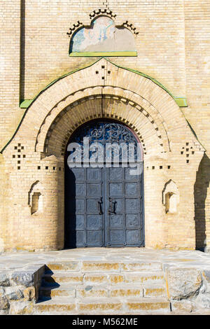 black metal gates of the ancient church. Stone stairs lead to the gate. over the gates of the image of the Holy - Stock Photo