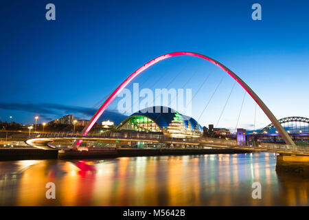 Newcastle upon Tyne UK, view at night of the Sage Gateshead building  and the floodlit Millennium Bridge spanning - Stock Photo