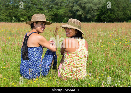Two women looking back in blooming meadow - Stock Photo