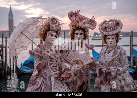Three people in traditional costume and painted masks, in front of the Grand Canal at St Marks Square during the - Stock Photo