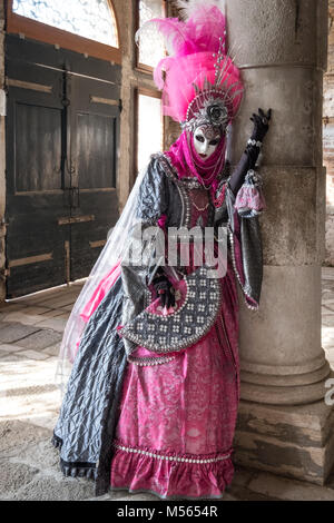 Lady in highly decorated mask and costume, standing against pillar during Venice Carnival (Carnivale di Venezia) - Stock Photo