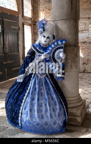 Woman in mask and highly decorative blue costume standing next to pillar in old, empty room during Venice Carnival - Stock Photo