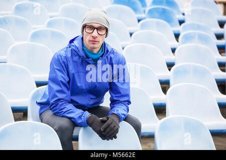 Portrait of professional athlete looking at camera sitting on stadium seat. - Stock Photo