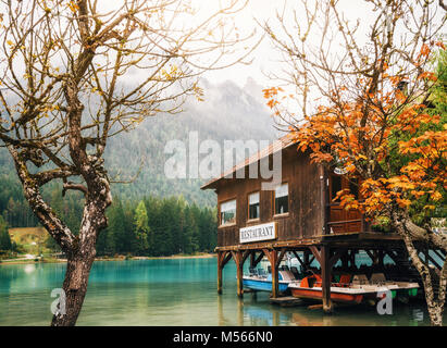 Dobbiaco Lake, Italy - 03 October, 2017: Lake Dobbiaco in the Dolomites with wooden boathouse restaurant on stilts - Stock Photo