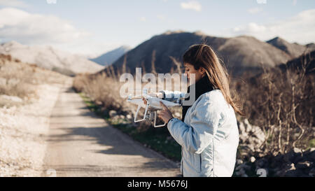 Young woman videographer catching flying aircraft with camera.Controlling landing of drone.Female filmmaker in nature - Stock Photo