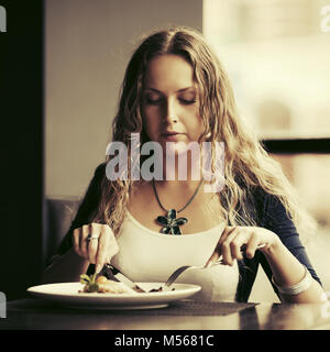 Beautiful young woman dining at restaurant - Stock Photo