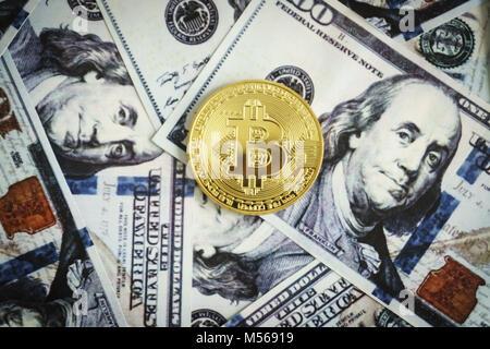 Gold coin bitcoin on hundred dollar bills - Stock Photo