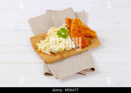 chicken schnitzels with potato salad on wooden cutting board - Stock Photo