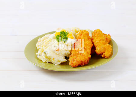 chicken schnitzels with potato salad on green plate - Stock Photo