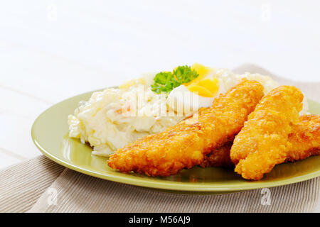 chicken schnitzels with potato salad on green plate - close up - Stock Photo