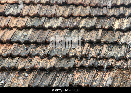 The roof is covered with brown tiles close up - Stock Photo