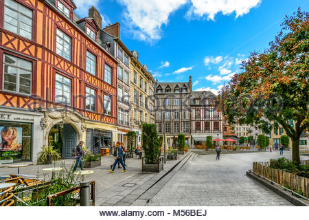 Timber frame homes line a town square in the medieval city of Rouen France with shops, a sidewalk cafe and tourists - Stock Photo