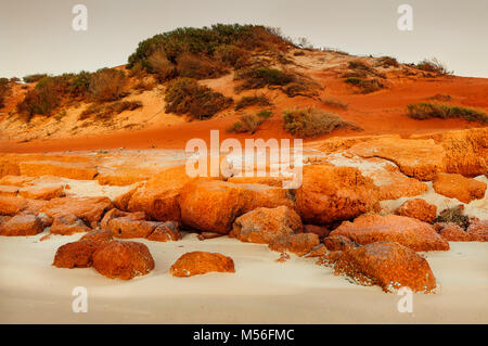 Red dunes at a white beach in Bottle Bay. - Stock Photo