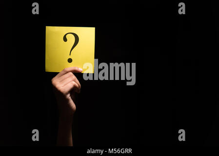 hand holding a yellow paper with question mark in a dark background - Stock Photo