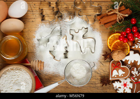 Christmas baking - flour, honey, eggs and gingerbread cookies on wooden table - Stock Photo
