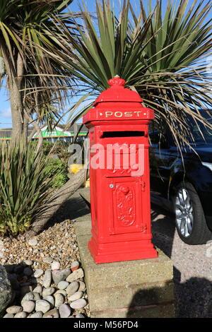 Cute bright red mini post box (pillar box) in a south coast of England in the sunshine - Stock Photo