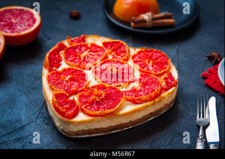 Baked cheesecake with red grapefruit slices in the shape of heart on the black stone background with ingredients - Stock Photo