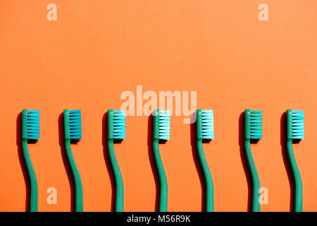 green toothbrushes in row, on orange with copy space - Stock Photo