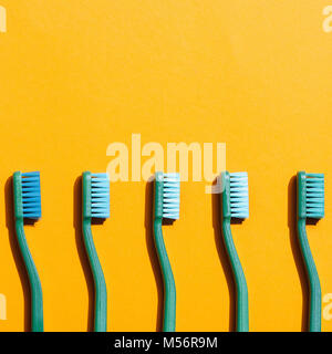 green toothbrushes in row, on yellow with copy space - Stock Photo