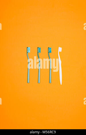 top view of green and white toothbrushes in row, isolated on orange - Stock Photo