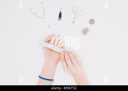 cropped image of woman filing nails with nail file isolated on white - Stock Photo
