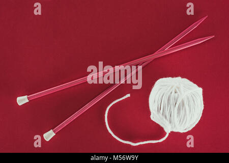 top view of white wool ball and knitting needles, isolated on red  - Stock Photo