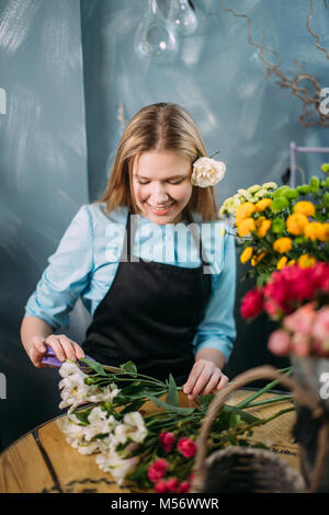 pretty girl putting white flowers on the table - Stock Photo