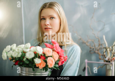 closeup shot of good-looking blond woman standing with roses - Stock Photo