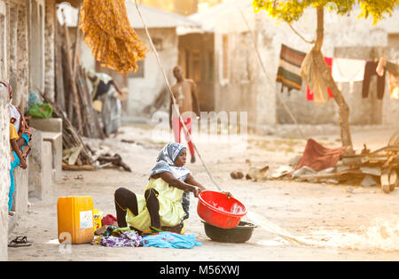 Stone Town, Zanzibar - January 20, 2015: Women throwing out her washing water and sitting on the floor - Stock Photo