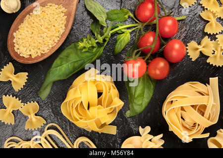 Overhead photo of different types of pasta on black - Stock Photo