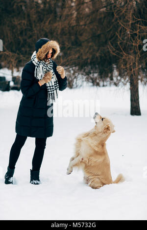 Photo of woman with retriever walking in winter park - Stock Photo