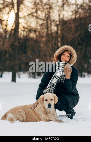Image of woman on walk with dog on background of trees in winter - Stock Photo