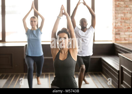 Group of young sporty people standing in Warrior one pose - Stock Photo