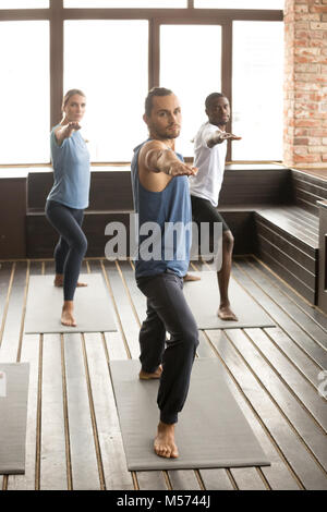 Group of sporty people standing in Warrior two pose - Stock Photo