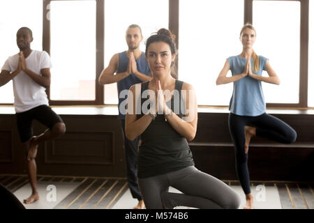 Group of sporty people in Vrksasana pose, close up - Stock Photo