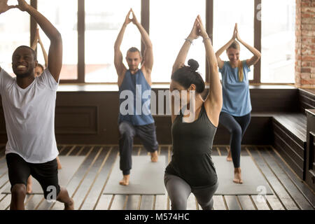 Group yoga in studio, diverse people doing exercises with instru - Stock Photo