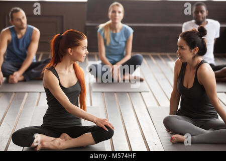 Two young beautiful fit women talking at group yoga training