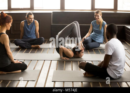 Multiracial people looking at instructor performing yoga pose at - Stock Photo