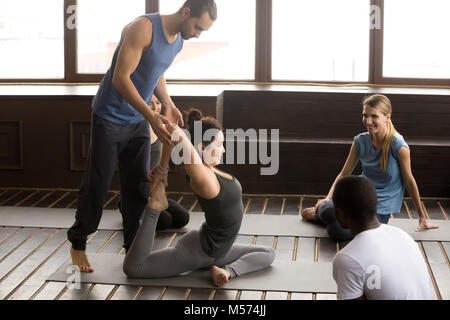 Instructor helping flexible woman doing yoga exercise at group c - Stock Photo