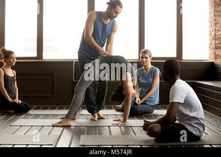 Male teacher assisting woman doing yoga bridge exercise on mat - Stock Photo