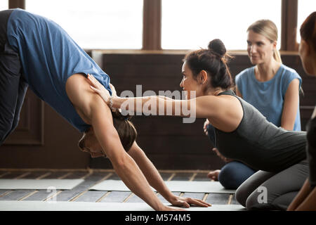 Yoga teacher helping man to stretch holding hands on shoulders - Stock Photo