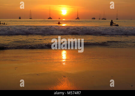 silhouette of ships sailing at sunset Nai Harn beach Phuket island - Stock Photo